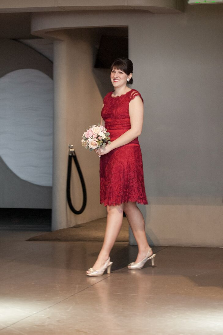 Greta's maid of honor, her sister, wore a knee-length, lacy red dress that complemented Greta's wedding dress.