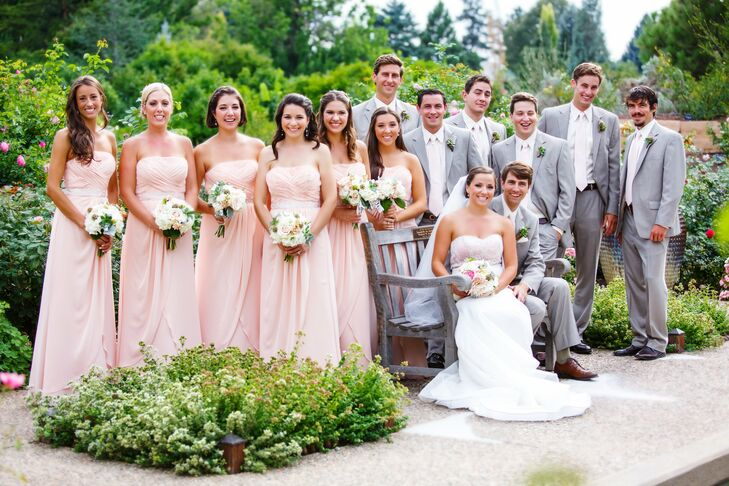 fec220f45469 Bridesmaids wore floor-length blush dresses with strapless necklines while  groomsmen donned light gray suits