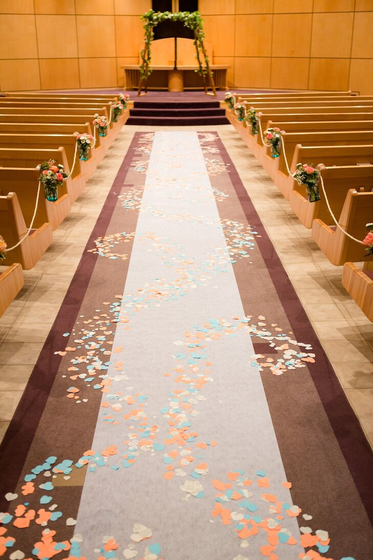 At the ceremony, the flower girls spread colorful heart-shaped paper as they walked down the aisle. The couple hand cut all of the paper, and Charles built the wood wedding arch garnished in garland.