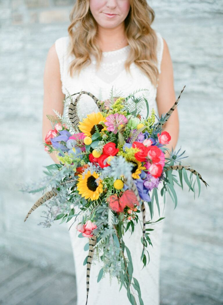 Bride holding bouquet with sunflowers and feathers