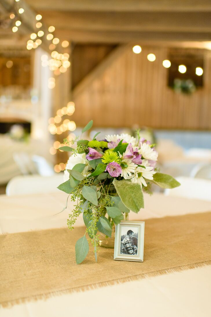 Mark and Amanda dressed their reception tables in ivory table cloths with burlap runners. Each table had a mason jar centerpiece with a photo of them.