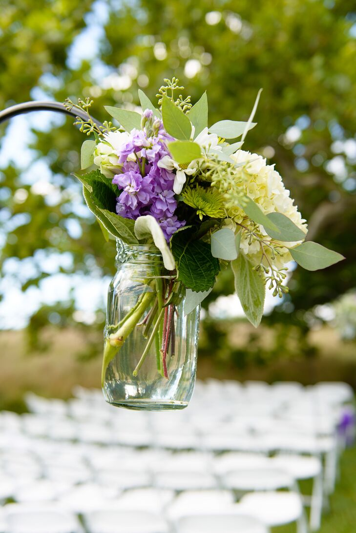 Mason jars hanging from shepherds' hooks while holding small bouquets of ivory and purple hydrangeas, calla lilies and roses lined the ceremony aisle.