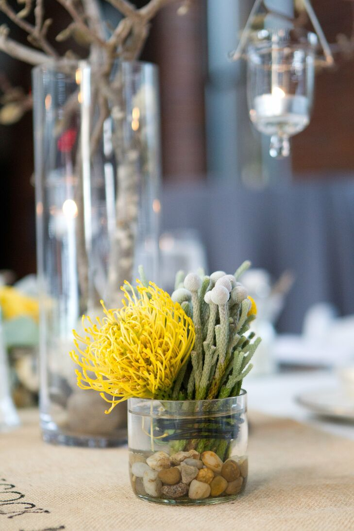 Small clear vases filled with pincushion protea and brunia berries sat next to the larger arrangements on the guest tables.