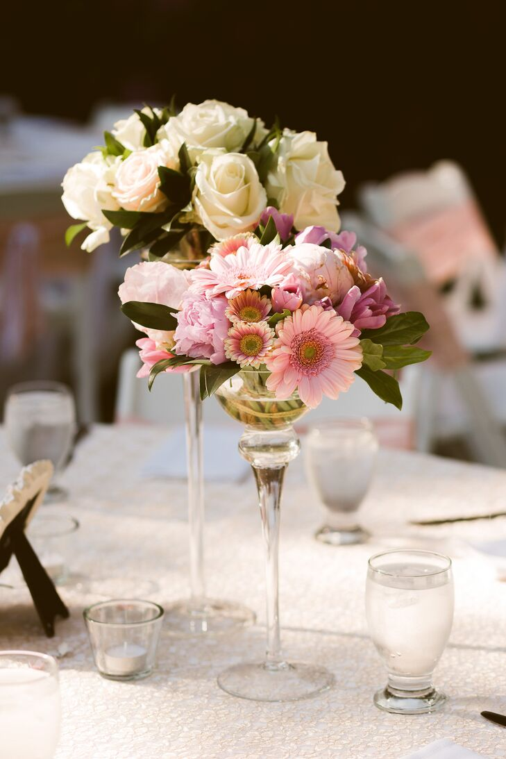 Small arrangements of ivory roses and pink gerbera daisies were displayed on the round tables for the reception centerpieces.