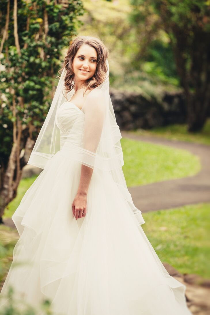 Steph wore a white strapless dress with a sweetheart neckline and a layered tulle skirt, which elegantly ruffled down to the floor. She paired the traditional dress with a fingertip-length tulle veil.