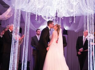 """""""The lit orbs and disco balls hanging from the sheer fabric huppah gave the first hint of the celebration to come,"""" says Michelle."""