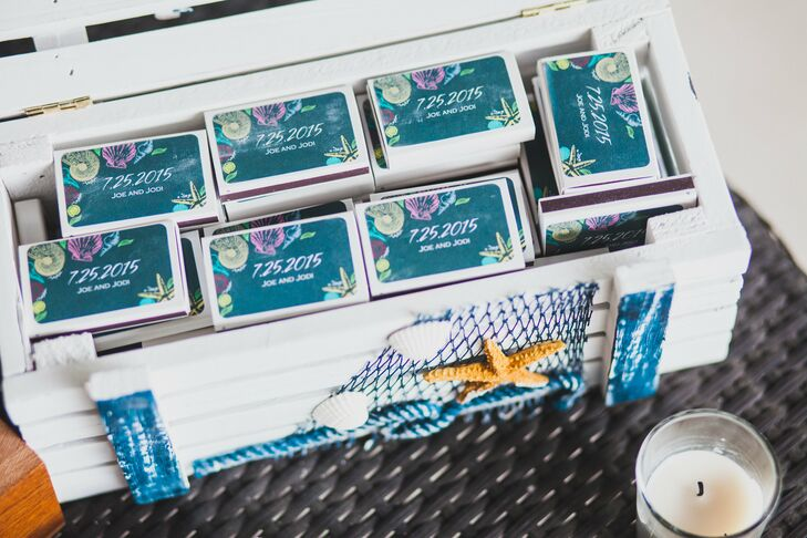Guests didn't expect this surprise at the reception: a custom DIY cigar bar. Next to an open wooden box of cigars, the couple had a white crate of personalized matchboxes. Each one fit their theme with bright seashells and a teal background.