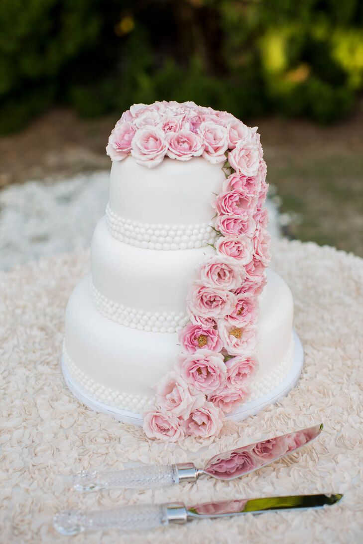 Great Cakes created this three-tier confection for dessert. Each tier was decorated with white pearl-style detailing around the bottom. Lots of pink roses topped the cake and cascaded down the side for added romance.