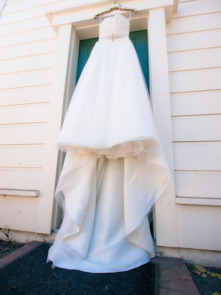 "Angela wore a strapless ivory wedding dress with a long train, designed by Cara Mia. ""What first drew me to my dress was that it has tiny dots all over it,"" says Angela. ""I loved that subtle but slightly quirky design element. It had just the right amount of glitz and unique elements, and it made me feel like a princess."""