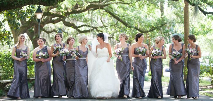 Amanda's bridesmaids wore long gray-purple trumpet-style dresses with a train. Her maid of honor and matron of honor chose strapless styles, and her bridesmaids wore sleeveless styles. A crystal belt and diamond drop earrings, both gifts from Amanda, completed their styles.