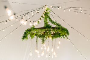 A Tent with a Greenery Chandelier and Edison Lights