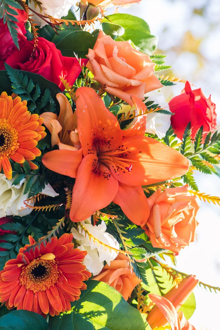The bouquets were gorgeous mixture of orange, red with accents of white and green, standing out against the charcoal dresses and suits.