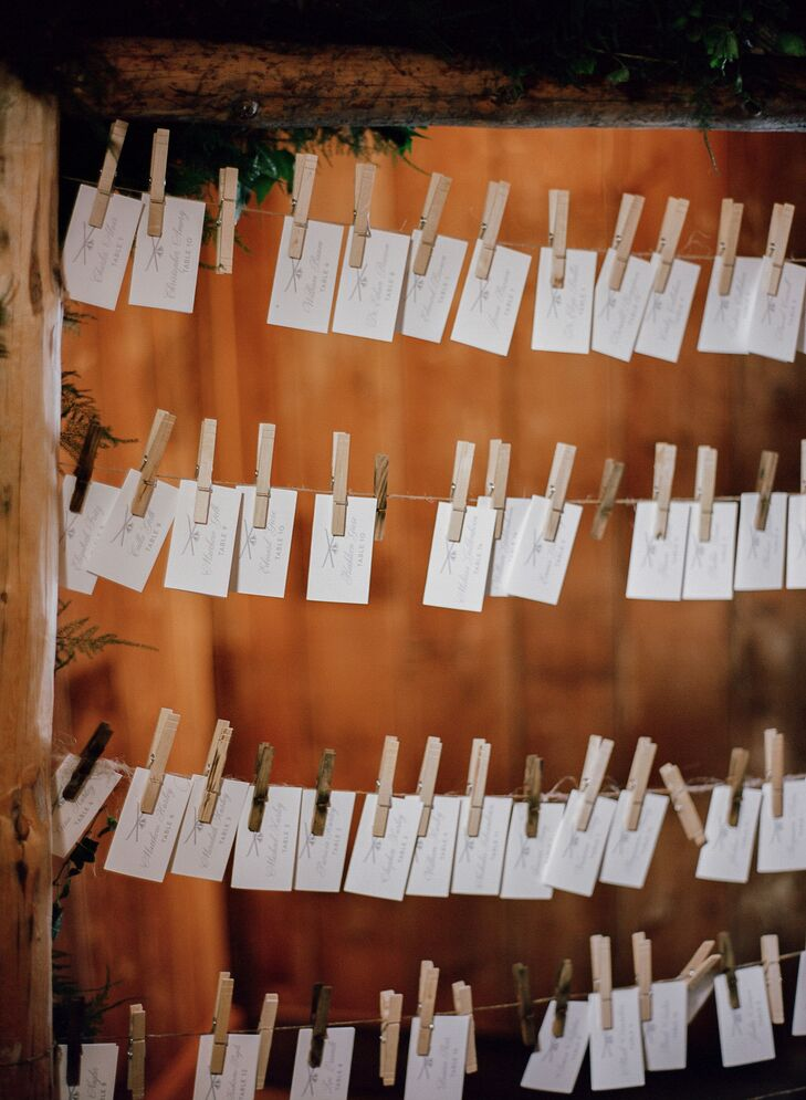 Rows of wire were strung across the inside of a rustic wooden frame creating the escort card display. The white escort cards were suspended from clothespins and Charlotte and Jeff's custom logo (their initials, a mountain and ski poles) was printed on each one.