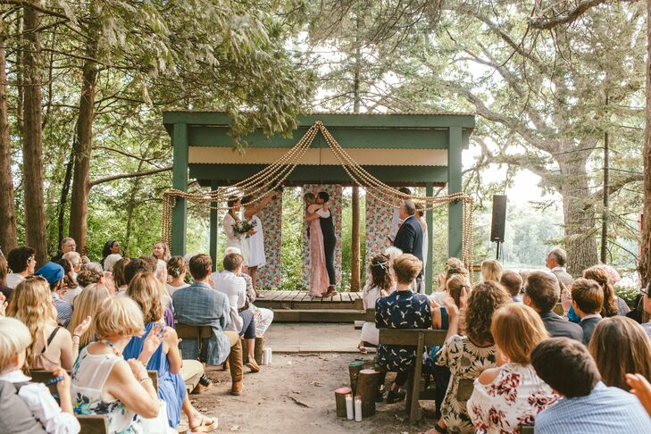 "Even though the camp is privately owned, there's a functioning outdoor church on the property—with benches overlooking a stage and scenic water views. ""It's incredibly beautiful and rustic,"" Ariana says. To add some color to the natural space, the couple created panels of wrapping paper as a backdrop, playing off the palette of gold, blush, blue and white. Their idea was to string greenery across the top of the structure, but after much deliberation, they decided to spray-paint ping-pong balls gold and tie them together to create garlands. rnLoved ones who have died were remembered with photos hung on a tree in the center of the aisle and candles that bridesmaids lit as they walked down the aisle, ""to symbolize the light of our loved ones being there on this special day,"" Ariana says."