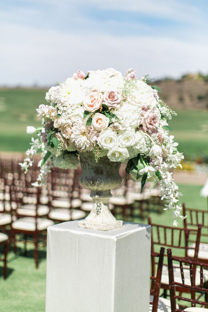 Two Grecian-style urns were placed at the ceremony's aisle entrance, both overflowing with ivory garden roses, white jasmine and blush pink peonies.