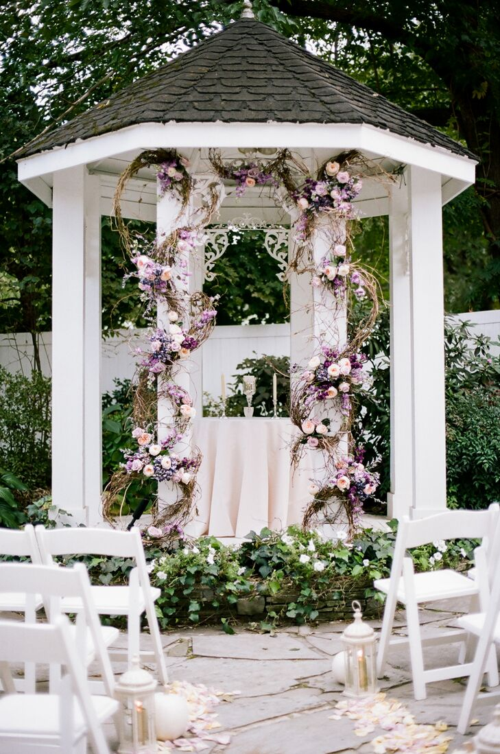 The ceremony's standout feature was the curly willow garland used to frame the garden's small white gazebo where the couple exchanged vows. Fancifully arranged willow vines dripped in full pink garden roses and purple stock, giving the decor a dramatic, yet utterly romantic vibe.