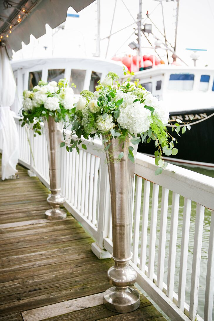 Two tall silver vases spilling with white hydrangeas, garden roses, ferns and other greenery flanked the altar space.