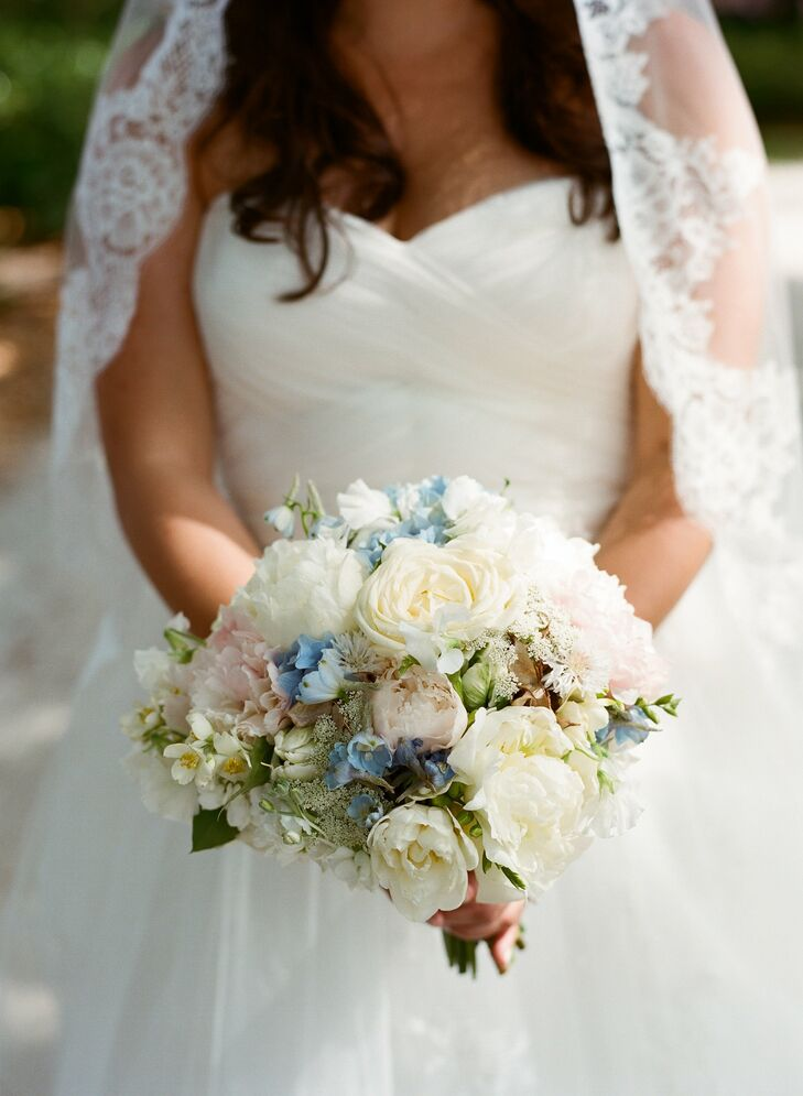 Kathryn's bouquet of crab apple, blue delphiniums, peonies and roses in muted pastel colors had a romantic, vintage feel.