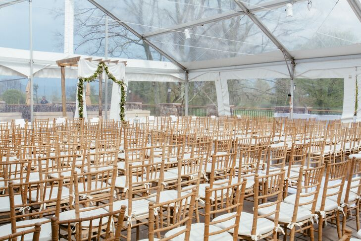 """Their ceremony was incredibly sweet with personal vows and an unexpected officiant - Mike's boss from NBC-NY. """"He was even better than we expected,"""" says Jenna.  """"It was light-hearted and personal, with lots of laughs throughout."""" Guests caught a great view of their tented ceremony from rows of neutral chiavari chairs."""