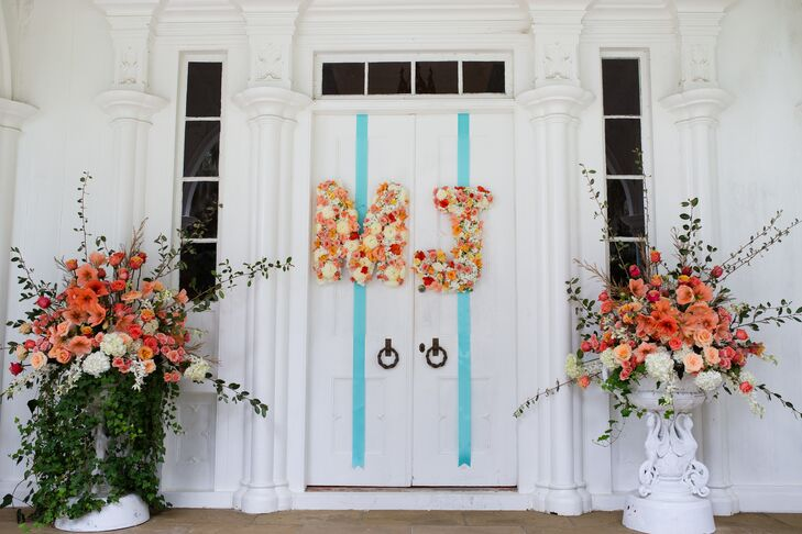 Madeline and Joe exchanged vows on the front porch of Rose Hill Mansion in Bluffton, South Carolina. They loved the natural red brick walkway and stunning house as the backdrop. They decorated their altar with two white urns filled with pink flowers and cascading ivy. The double doors included the letters M and J for their initials, which were also adorned with lush flowers in the wedding colors.