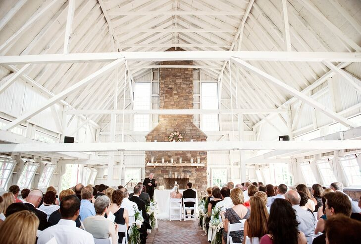 "The couple chose The Ashford Estate because they could have the entire venue to themselves, and it was important to Lauren and Aaron to honor their New Jersey roots by getting married in their home state. The ceremony took place in a rustic barn, which has exposed wood beams and a stone fireplace. The brick herringbone floor created a dramatic aisle runner. ""I kept the ceremony decorations minimal since I felt like the building was unique and could speak for itself,"" Lauren recalls."
