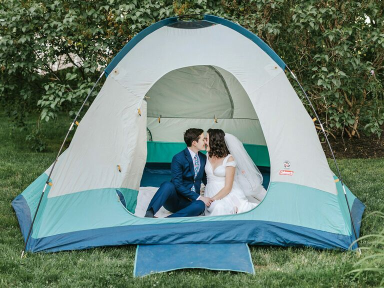 Bride and groom sitting in tent at camp-inspired outdoor summer backyard wedding
