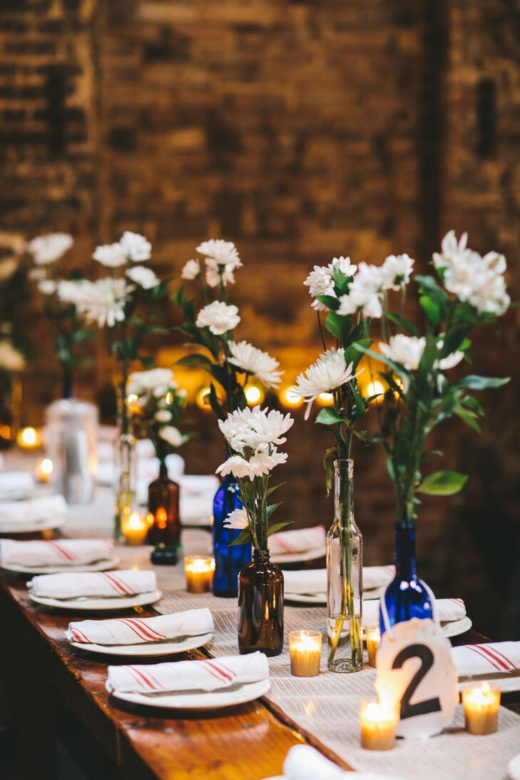 """Clear, blue and brown bottles were filled with ruscus and white blooms purchased at the grocery store. Bridal bouquets also doubled as centerpieces. """"I love how all the white and green looked in the dark, contrasty room,"""" Amanda says."""