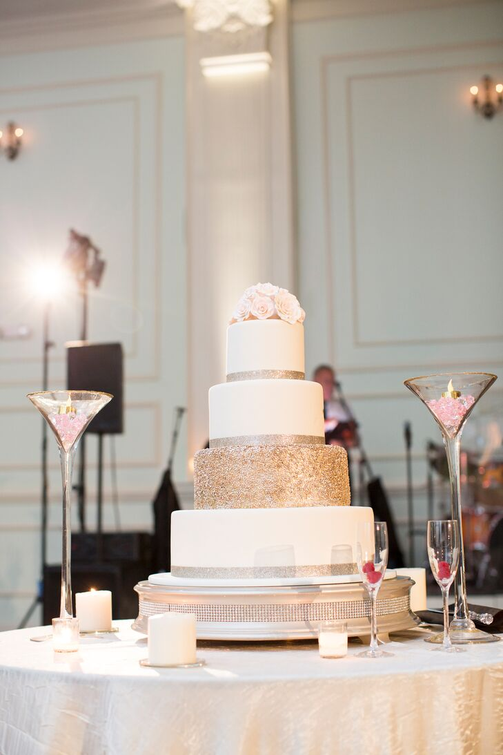 Their wedding cake was just as glam as its surrounding martini glass accents. Almost every ivory fondant tier was wrapped in gold glitter ribbon along the base. Instead of ribbon, gold beading covered the third layer, giving it that extra sparkle. Classic blush roses also topped the confection.