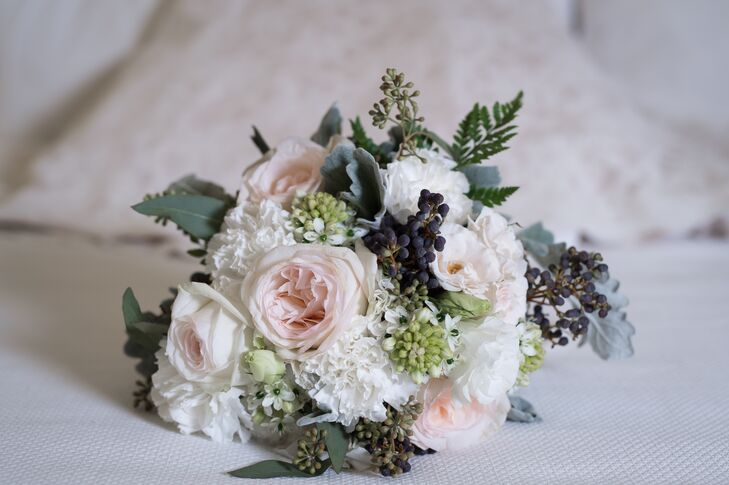 Wanting a  natural forest-inspired bouquet, Bianca walked down the aisle with an arrangement of white roses, white garden roses, white peonies, green hypericum berries, dusty miller, seeded eucalyptus and assorted berries made by The Wifestylist.