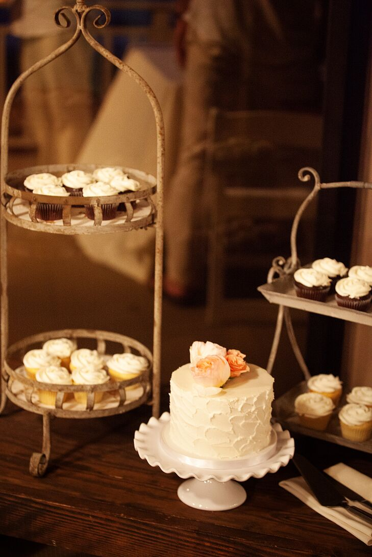 An ivory wedding cake filled with strawberry lemonade flavoring was served on a simple white cake stand. Vanilla and chocolate cupcakes were assorted on two wood tiers.