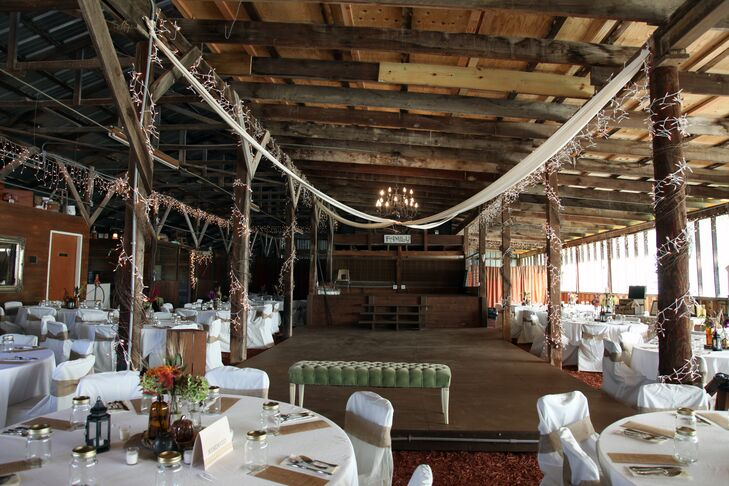 Melissa and Michael decorated the inside of Gallagher Barn with christmas lights, white drapery and burlap chair wraps for a festive, rustic feel.