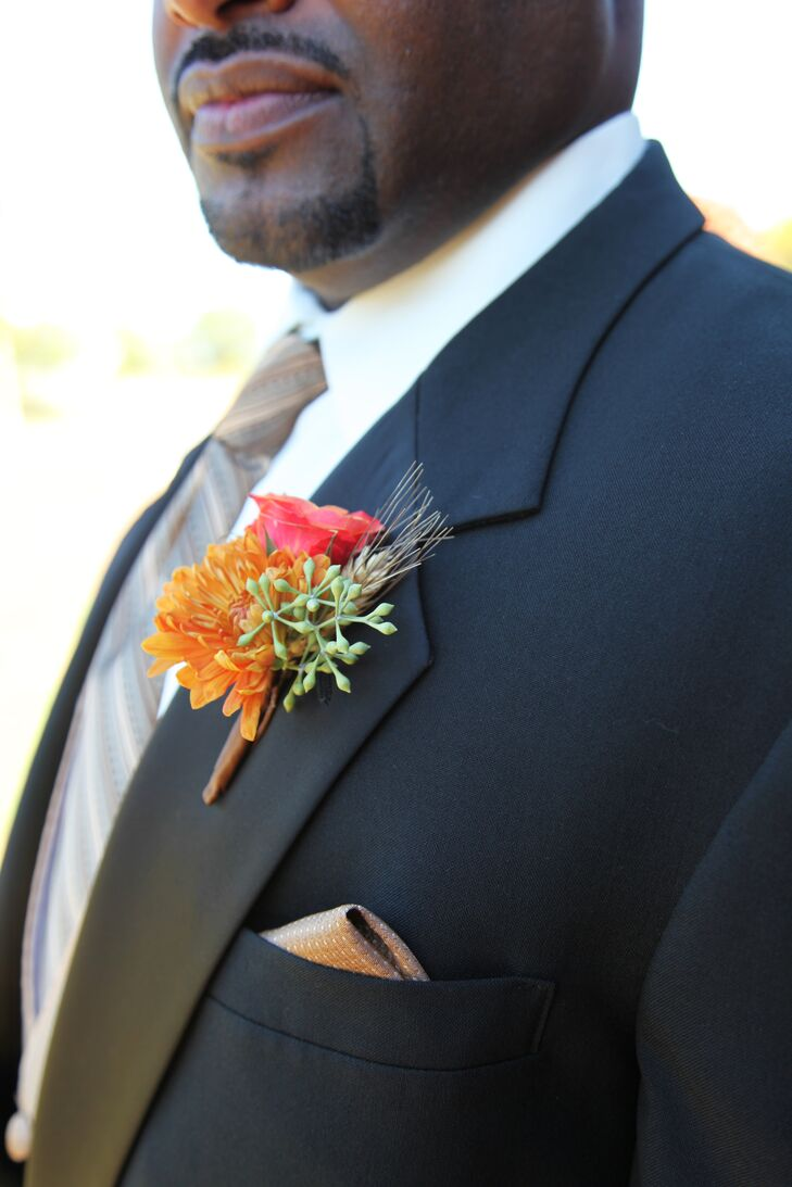Michael wore a orange dahlia, coral rose, seeded eucalyptus and dried wheat on his lapel to match the rustic barn theme.