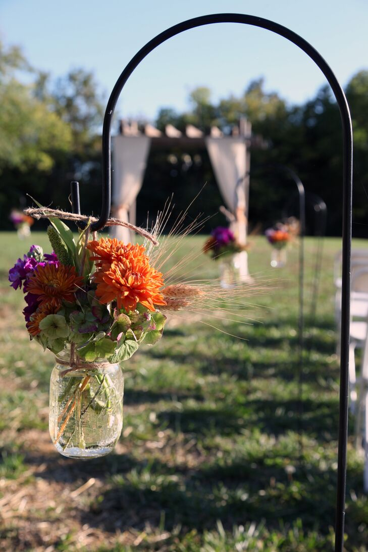 Mason jars were filled with orange dahlias and hung from shepherd hooks with burlap twine.