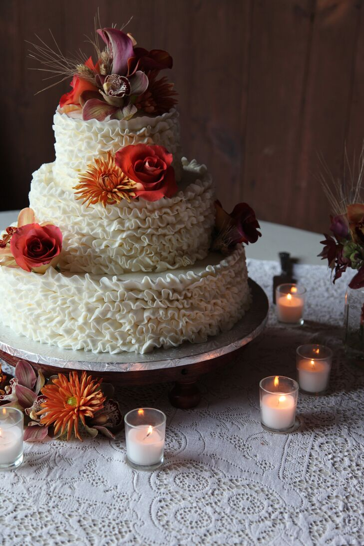 Melissa and Michael enjoyed a white ruffled butter cream wedding cake topped with fresh roses, dahlias, orchids and wheat.