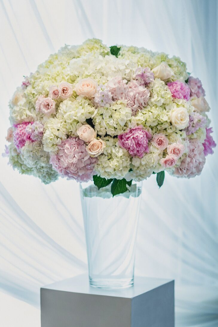 A lush arrangement of white and pink roses and hydrangeas were displayed on tall clear vases for the flower decor.