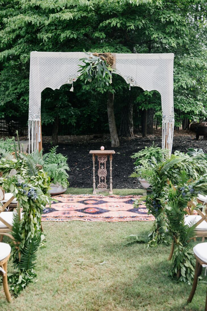 Bohemian Backyard Ceremony with Antique Rug and Greenery Aisle Decorations