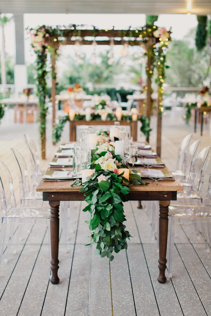 """As for the reception decor, Kristin and Andrew knew they wanted wooden family-style tables. """"We thought it fit right in with the raw and unearthed feeling of the Perez Art Museum,"""" Kristin says. Each one beautifully blended into their garden theme and matched the wooden structure that surrounded their sweetheart table."""