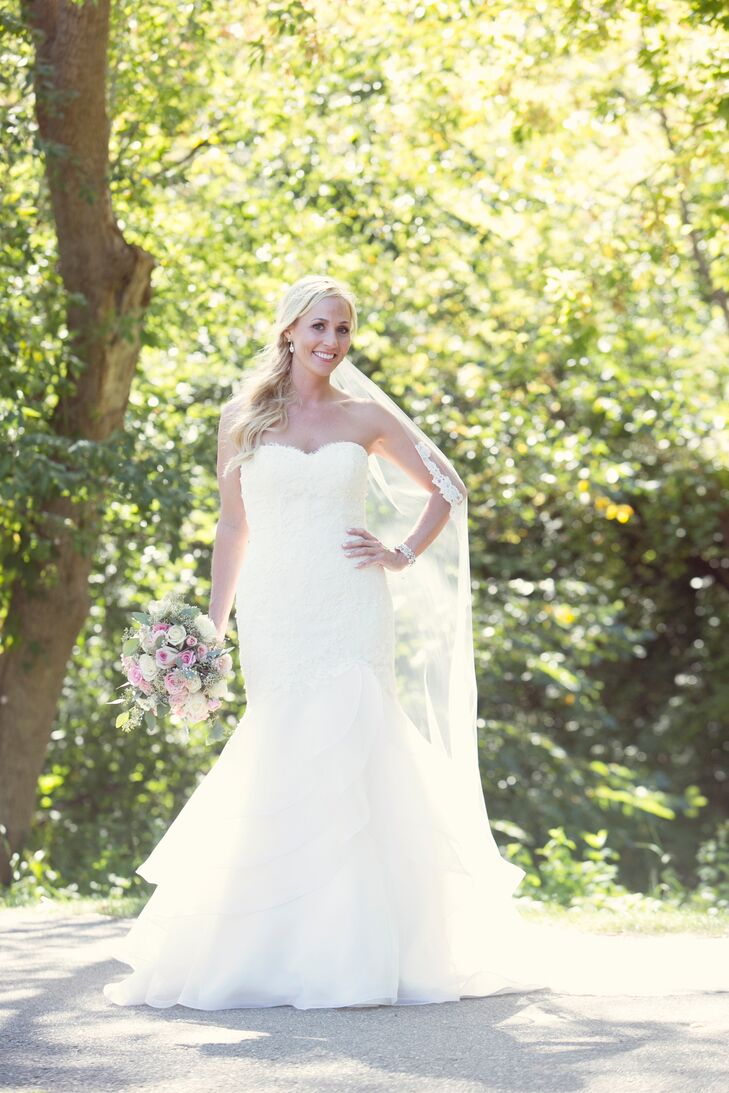 Katie wore a strapless, lace, mermaid-fit dress by Paloma Bianca and paired it with a cathedral-length veil. She had the plain bust custom-beaded to match the sparkly theme of her wedding.