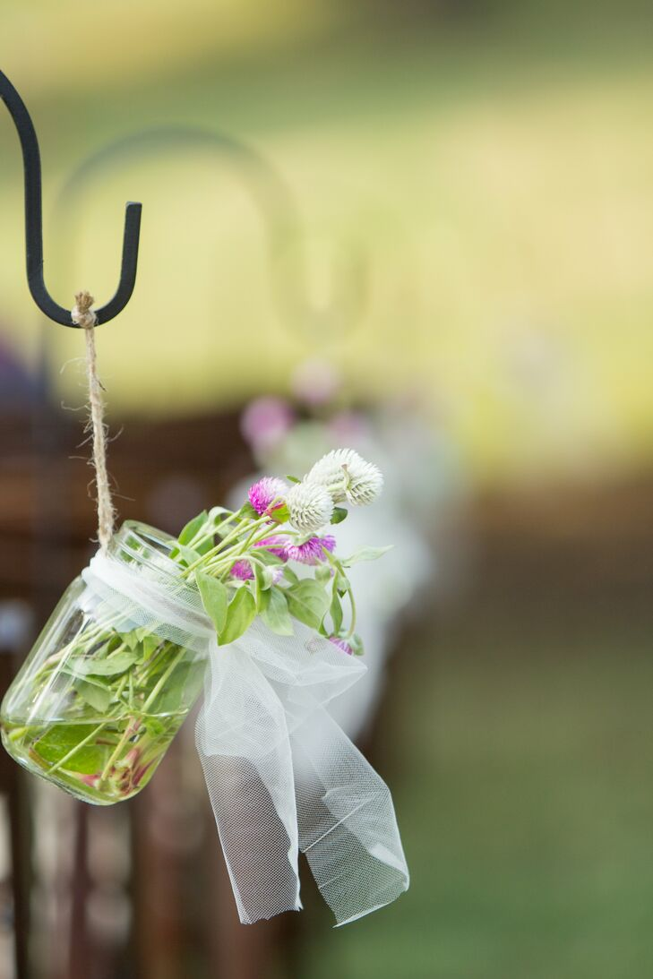 The bride took a hands-on approach to her floral decorations by purchasing them at the local farmer's market and creating her own bouquets and aisle markers.