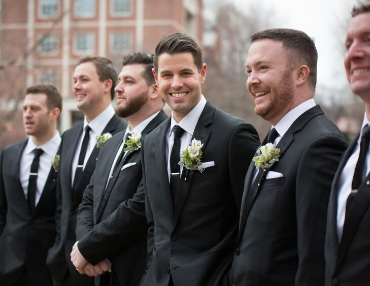 Jake and his groomsmen wore tuxedos from The Black Tux, a website similar to Rent the Runway that allowed them to rent matching attire for the wedding at a fraction of the retail price. They accessorized with skinny black ties and white alstroemeria boutonnieres.