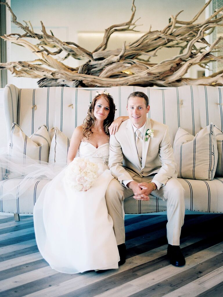 Bride and groom in a nautical setting on a blue stripe couch with driftwood behind them