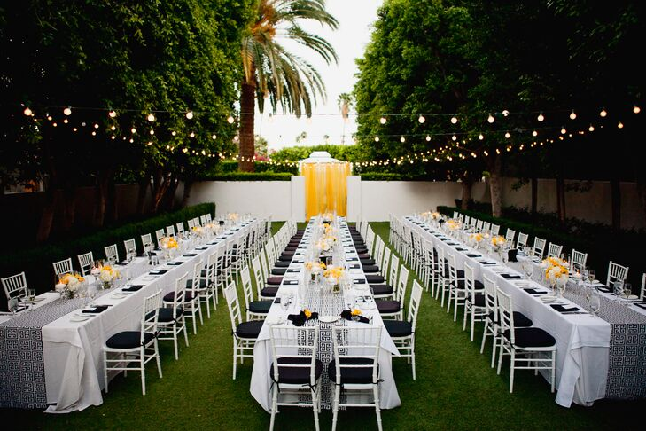 The reception took place outside, where string lights hung over long, white dining tables that were draped with black-and-white runners depicting the Greek key design.