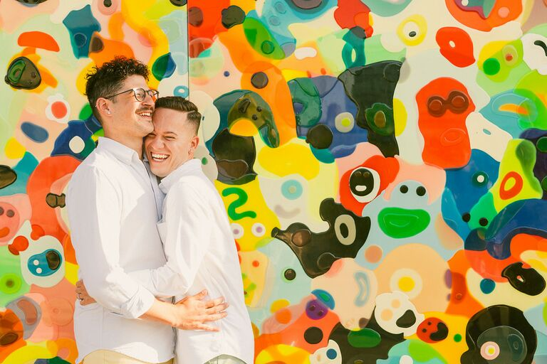 Grooms hugging in front of colorful mural