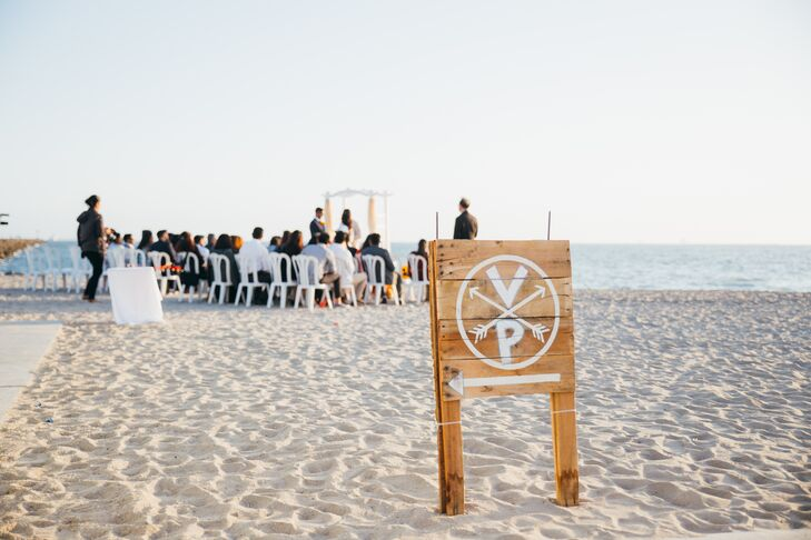 "The beach and setting sun served as the primary backdrop for the ceremony. Though decor was minimal, handcrafted wooden signs helped lead guests to the ceremony site. ""We wanted the wedding to have a close-to-home, DIY, made-with-love feel to it,"" Vidya says. ""We barely had to decorate because the setting was so beautiful."""