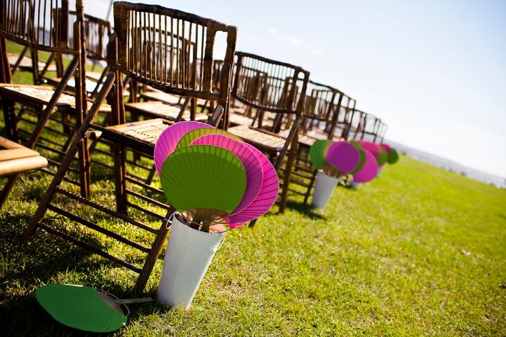 To keep guests cool during the ceremony, Sandra and Tim provided fans for their guests. The bright pink and green fans were placed in baskets at the end of each row.
