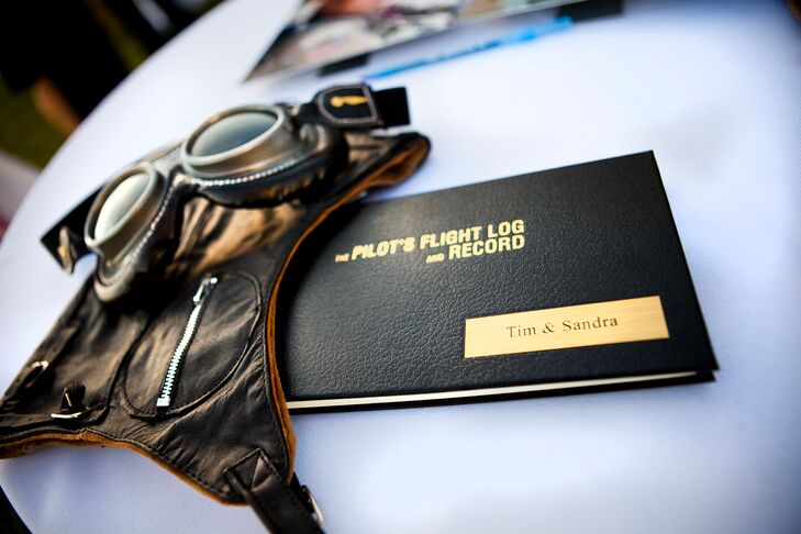 The couple chose an aviation inspired guest book for guests to sign. The book was actually a pilot log book, which they styled with a pair of vintage flying goggles.