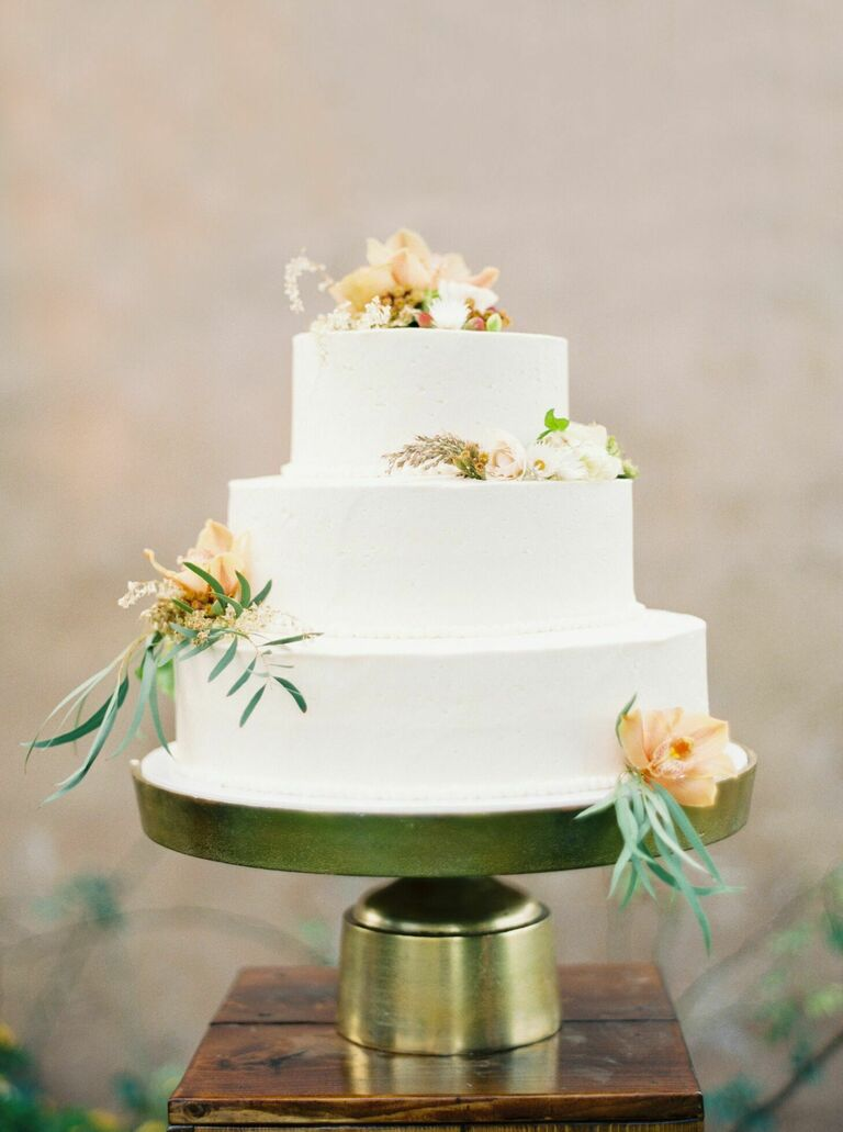 Modern three-tier cake sitting on gold cake stand