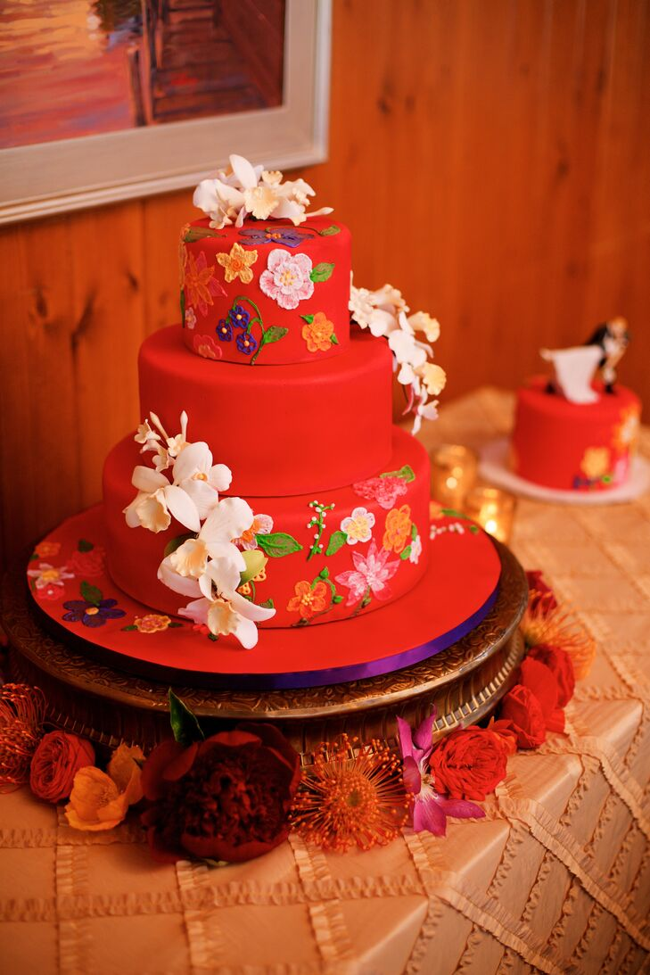 The multitier red cake featured white sugar paste orchids climbing the sides of the fondant, with a topper of a groom dipping his bride (placed on a tier off to the side). The cake flavors were coconut with cherry and chocolate buttercream, and chocolate with salted caramel and chocolate buttercream.