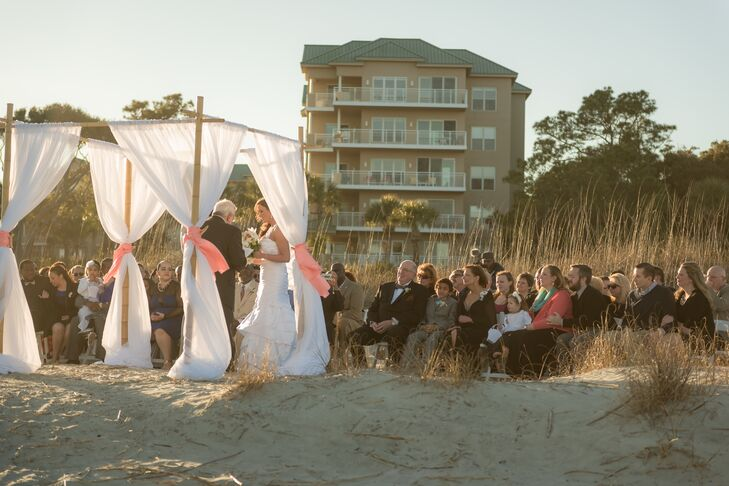 """The ceremony was held on the beach near sunset at Hilton Head Island. Chairs were set up in front of the tall grass on the beach and facing water. They defined the altar area with a simple wooden pergola draped in white linens and tied with coral ribbon on four sides. """"We had a special ceremony that highlighted our close family and friends,"""" Bethany says."""