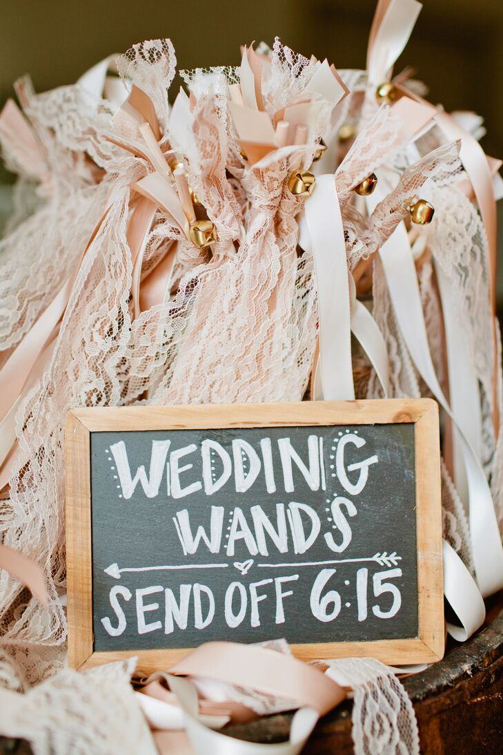 The bride and groom had DIY wooden wedding wands with pastel pink and cream lace streamers for their guests to wave in the air during their final sendoff at the end of their courtyard reception.